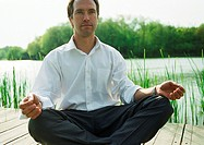 Businessman in lotus position, outdoors