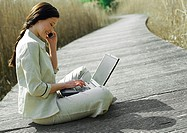 Businesswoman sitting with laptop computer, outdoors