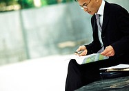 Businessman sitting outdoors, examining documents