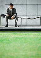 Businessman on bench looking at cell phone