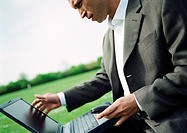 Businessman using laptop computer outdoors, close-up