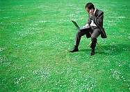 Businessman sitting on chair in grassy field with laptop and cell phone