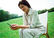 Businesswoman using cell phone on chair outdoors, close-up