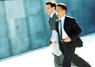 Two businessmen walking outdoors, blurred motion