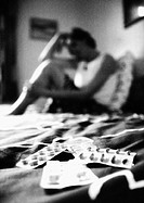 Woman sitting on bed, pills in foreground, blurred, b&w