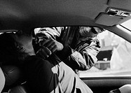 Man holding gun to woman's neck through car window, b&amp;w