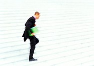 Businessman running down steps, side view, blurred motion