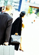 Businessman and businesswoman holding briefcases, rear view, blurred
