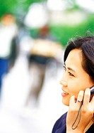 Businesswoman using cell phone, close-up, blurred background (thumbnail)
