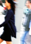 Businesswoman walking, side view, blurred