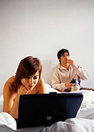Woman working on laptop computer in bed, man eating