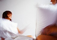Woman and man having pillowfight, blurred