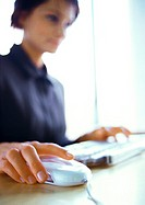 Businesswoman working on computer, blurred, focus on hand on mouse in foreground