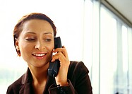 Businesswoman on phone, smiling, head and shoulders, close-up
