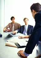 Business people looking at businessman standing