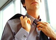 Businessman undoing tie, close-up, low angle view