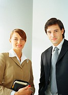 Businesswoman standing next to businessman, waist up