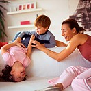 Children playing with mother on couch