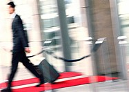 Businessman walking with luggage, side view, blurred
