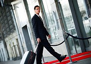 Businessman walking with luggage outside, side view (thumbnail)