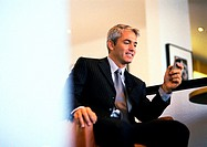 Businessman sitting holding cell phone (thumbnail)