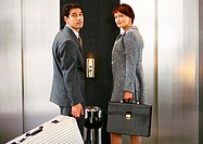 Businessman and businesswoman waiting for the elevator, looking over shoulders at camera