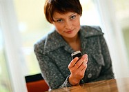 Businesswoman holding cell phone, looking at camera