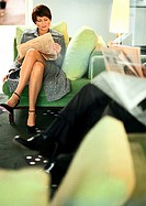 Businesspeople sitting reading newspaper