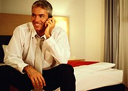 Businessman sitting on bed, talking on cell phone
