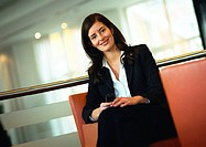 Businesswoman sitting, smiling at camera, portrait, tilt