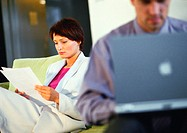 Businesswoman looking at document near businessman on computer, blurred