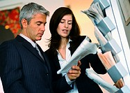 Businessman and businesswoman looking at newspaper