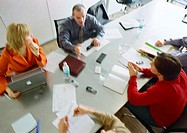 Group of business people sitting at table having a meeting, view from above, blurred