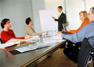 Business people sitting at table in meeting, blurred