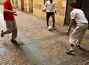 Men kicking soccer ball in street