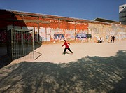Person playing soccer on dirt yard next to graffiti wall