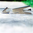 Stapler and staple remover on ground