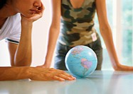 Two people looking at globe on table