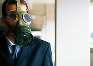 Portrait of businessman with gas mask covering face