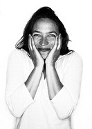 Woman laughing into camera, hands on cheeks, portrait, b&w