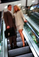 Business couple on escalator