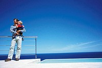 Father holding toddler while enjoying a view of the sea