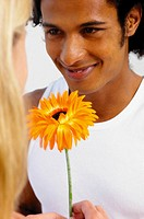 Man giving flower to woman