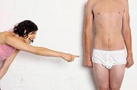 Woman laughing at man in underwear