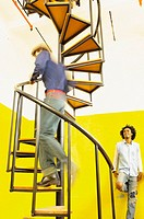 Man going up spiral stairs