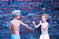 Boys fighting against wall