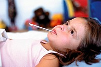 Girl with thermometer in mouth