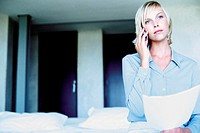 Woman sitting on bed with cellphone