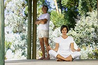 Woman doing yoga outside with man standing