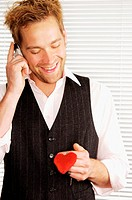 Smiling man holding heart shaped keyring (thumbnail)